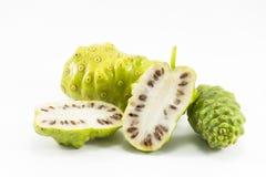 Noni e fatia do noni isolada no fundo branco Fruto para a saúde e a erva Imagem de Stock