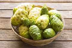 Noni fruit  in the basket on wooden table.Fruit for health and herb for health Stock Photography