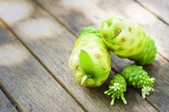 Noni fruit and blossom on old wooden table.Fruit for health and detox. 1 Royalty Free Stock Photography