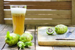 Noni fruit and noni juice and blossom on old wooden table.Horizontal. 1 Royalty Free Stock Images