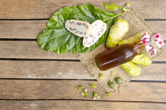 Noni fruit and noni juice on wooden table.Fruit for health and herb. For health Stock Photo