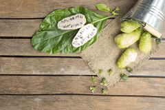 Noni fruit in tank on wooden table.Fruit for health and herb. For health Stock Images