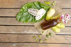 Noni frukt och nonifruktsaft på trätabellen Frukt för hälsa och ört arkivfoto