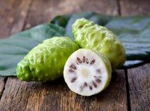 Noni frukt på trä royaltyfri fotografi