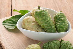 Noni Herbal Fruit on the Plate and wood floors. Royalty Free Stock Photography