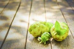 Noni okwitnięcie na starym drewnianym stole i owoc z bliska Obraz Royalty Free