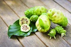Noni owoc z noni plasterkiem i okwitnięcie na starym drewnianym stole Zdjęcie Stock