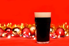 Pint glass of dark beer or stout ale with christmas lights baubles and tinsel on red background. Nonik pint glass of dark beer or stout ale with christmas lights stock photos