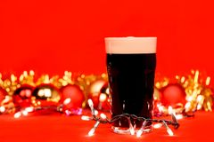 Dark ale beer in pint glass with christmas baubles tinsel and li. Nonik pint glass of dark beer or stout ale with christmas lights baubles and tinsel on red stock photography