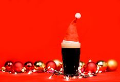Pint glass of dark beer or stout ale with red santa hat christmas lights baubles and on red background. Nonik pint glass of dark beer or stout ale with red santa stock photography