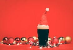 Pint glass of dark beer or stout ale with red santa hat christmas lights baubles and on red background. Nonik pint glass of dark beer or stout ale with red santa royalty free stock image