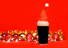 Pint glass of dark beer or stout ale with red santa hat christmas lights baubles and tinsel on red background. Nonik pint glass of dark beer or stout ale with stock photography
