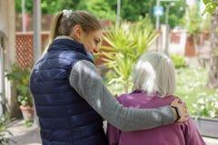 Nonna anziana d'abbraccio della giovane donna attraente all'aperto - Generazioni - amore femminile fotografie stock libere da diritti