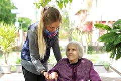Nonna anziana d'abbraccio della giovane donna attraente all'aperto - Generazioni - amore femminile immagini stock libere da diritti