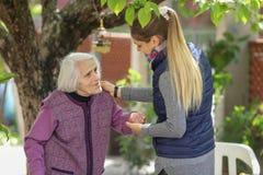 Nonna anziana d'abbraccio della giovane donna attraente all'aperto - Generazioni - amore femminile immagini stock