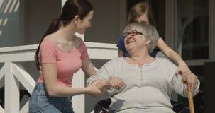 Nonna anziana d'aiuto per camminare nipote e figlia che prendono cura della donna anziana pensionata che sorride insieme sul colp video d archivio