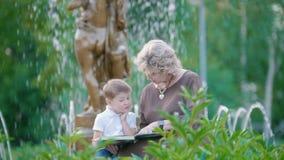 Nonna attraente e ragazzino che leggono un libro vicino alla fontana nel parco di estate stock footage