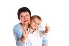 Nonna che abbraccia il suo nipote su un fondo bianco, dante segni Fotografia Stock