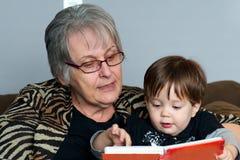 Nonna che legge al nipote Immagine Stock