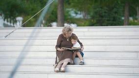 Nonna che legge un libro al suo nipote che si siede sulle scale nel parco archivi video