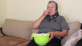 Nonna che mangia popcorn dalla ciotola video d archivio