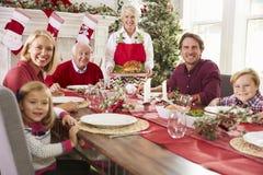 Nonna che mette in evidenza la Turchia al pasto di Natale della famiglia Fotografia Stock