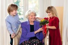 Nonna che riceve i fiori dai nipoti Immagine Stock