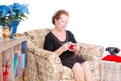Nonna che si siede a casa facendo suo tricottare Fotografia Stock