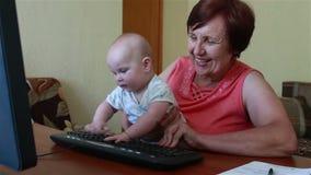 Nonna che tiene un bambino, gioca con la tastiera di computer video d archivio