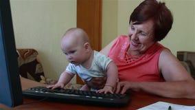 Nonna che tiene un bambino, gioca con la tastiera di computer stock footage