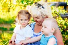 Nonna con due bambini in natura, fuoco sulle donne Fotografia Stock