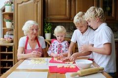Nonna con i grandkids che cucinano nella cucina Immagine Stock