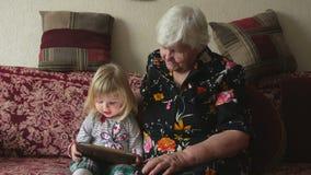 Nonna con la ragazza del todler che guarda le immagini stock footage