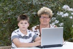 Nonna con un nipote dietro il computer portatile all'aperto fotografie stock