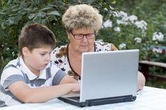 Nonna con un nipote dietro il computer portatile all'aperto fotografia stock libera da diritti