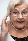 Nonna curiosa che esamina macchina fotografica immagine stock
