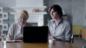 Nonna d'istruzione del nipote come utilizzare un PC del computer portatile Sorridono e ridono archivi video