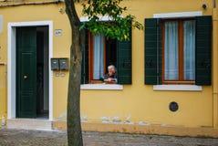 Nonna die uit Venster, Burano, Venetië, Italië kijken stock afbeelding