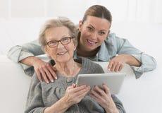 Nonna e giovane gran-figlia con la compressa digitale Fotografia Stock