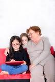 Nonna e nipoti che per mezzo del PC della compressa Fotografia Stock