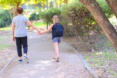 Nonna felice e nipote che camminano alla scuola sulla via nel parco di autunno immagine stock