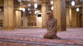 Nonne dans la robe longue se reposant sur votre recouvrement et sourires à l'intérieur d'une mosquée islamique ?gypte clips vidéos