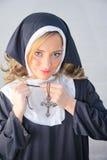 Nonne, die auf christliches Kreuz sich setzt Stockbild
