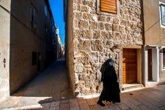 Nonne, die in die alte Stadt geht Stockbilder