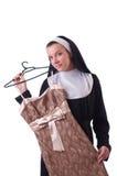 Nonne, die Kleidung auf dem Aufhänger lokalisiert wählt Lizenzfreie Stockbilder