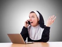 Nonne, die an Laptop - religiöses Konzept arbeitet Stockfoto