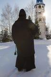 Nonne hält ein Rosenbeet in den Händen nahe Glockenturm im orthodoxen Kloster, Russland Stockfotografie