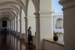 Nonne im Kloster schaut aus Fenster heraus lizenzfreie stockbilder