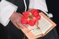 Nonnenhände mit Blume auf Bibel Lizenzfreie Stockfotografie