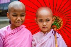 Nonnes dans des robes longues roses avec le parapluie de papier rouge Images libres de droits